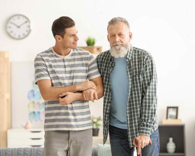 a caregiver assisting a senior man walk