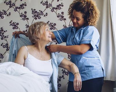 a caregiver helping a senior woman get dressed