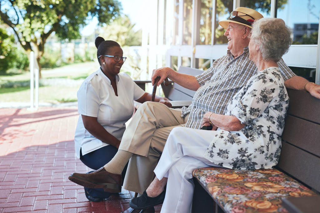 a senior man and a senior woman relaxing outside accompanied by their caregiver