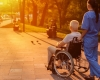 a caregiver and a senior man in a wheelchair looking at the sunset