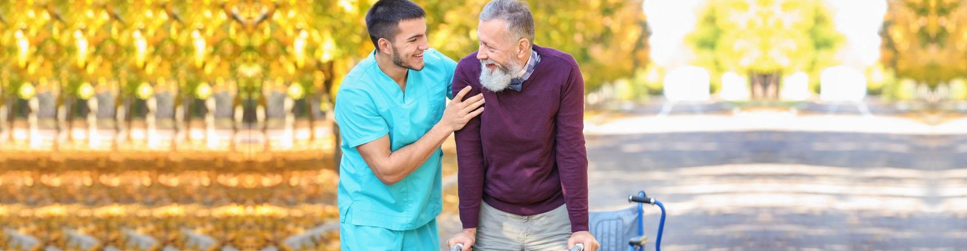 a caregiver accompanying a senior man walk outside