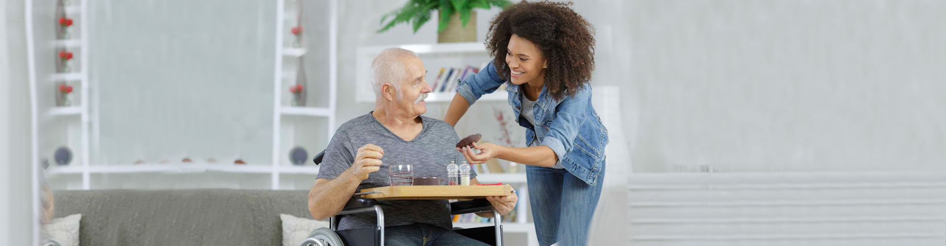 a caregiver giving medicine to the senior man