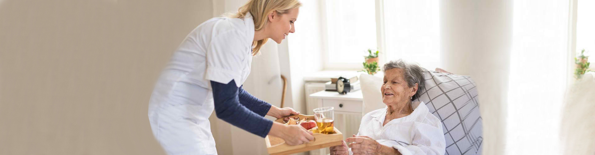 a caregiver serving meal to the senior woman in bed